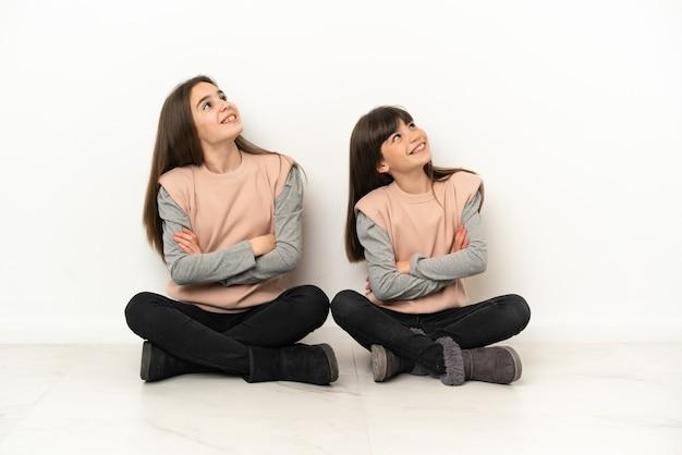 Siostrzyczki siedzi na podłodze na białym tle na białym tle patrząc uśmiechając się