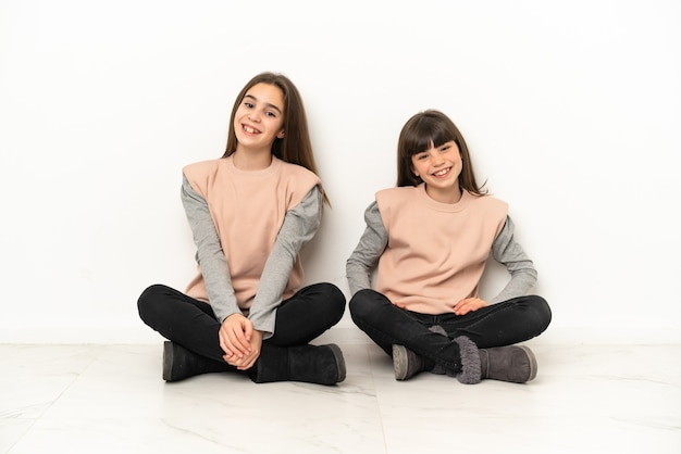 Siostrzyczki siedzi na podłodze na białym tle na białym tle pozowanie z rękami na biodrze i uśmiechnięty