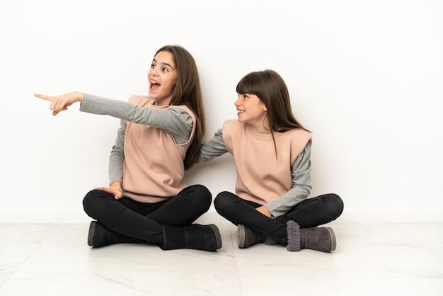 Siostrzyczki siedzi na podłodze na białym tle na białym tle, prezentując pomysł, patrząc w kierunku uśmiechniętym