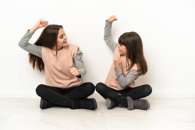 Siostrzyczki siedzi na podłodze na białym tle świętuje zwycięstwo w pozycji zwycięzcy