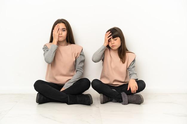 Siostrzyczki siedzi na podłodze na białym tle z zaskoczeniem i zszokowany wyraz twarzy