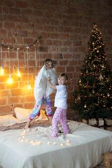 Siostrzyczki w piżamie na łóżku walczą z poduszkami