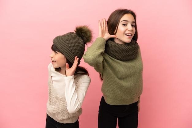 Siostrzyczki w zimowych ubraniach na białym tle na różowym tle, słuchając czegoś, kładąc rękę na uchu
