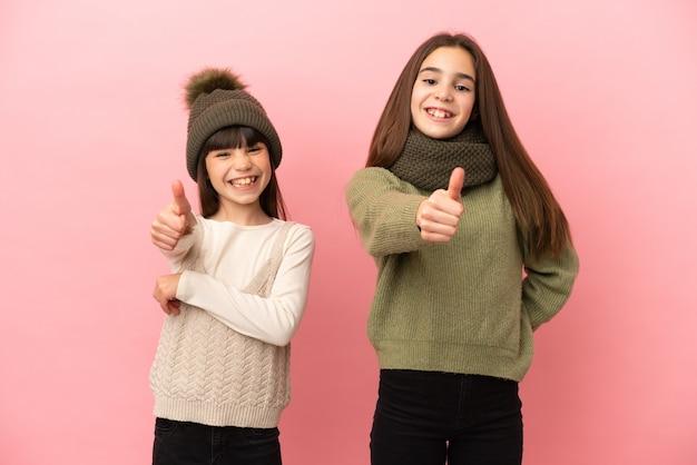 Siostrzyczki w zimowych ubraniach na różowym tle z uniesionym kciukiem, bo stało się coś dobrego