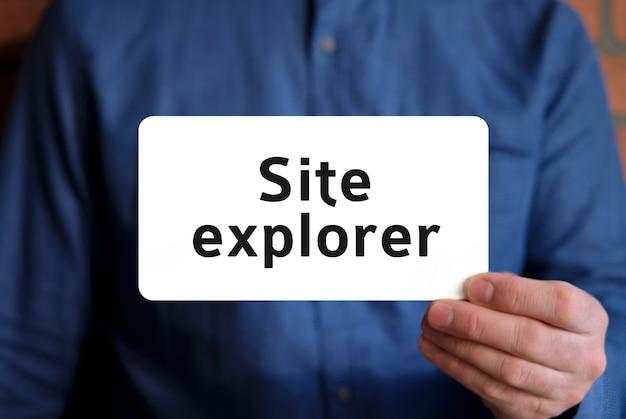 Site explorer tekst na białym znaku w dłoni mężczyzny w niebieskiej koszuli