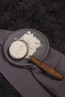 Sitko z drewnianą rączką z mąką w betonowej płycie na czarnym tle. kłosy pszenicy i lniana serwetka. przygotowanie do pieczenia