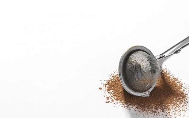 Sitko ze stali nierdzewnej na proszek czekoladowy na białym tle z miejsca kopiowania
