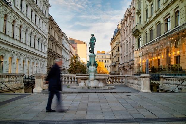 Sityscape z widokiem na fontannę goose girl o nazwie gansemadchenbrunnen w wiedniu, austria między domami i niewyraźne chodzenie po drugiej stronie ulicy.