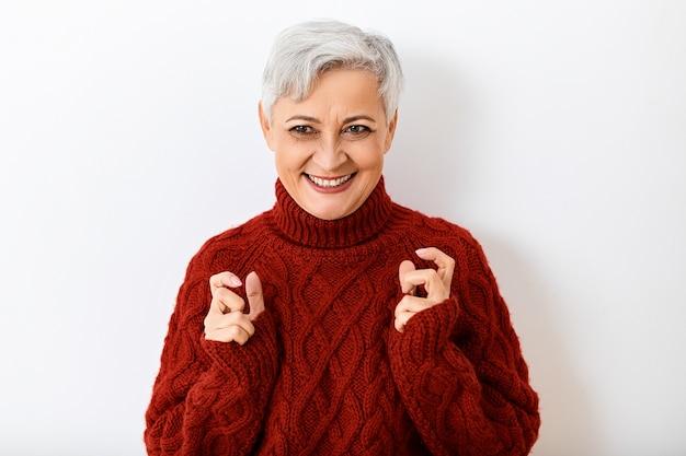 Siwa, dojrzała starsza kobieta w stylowym swetrze z dzianiny wyrażająca podekscytowanie i radość, patrząca z szerokim, promiennym uśmiechem, trzymająca się za ręce, jakby coś ściskała. ludzkie reakcje i uczucia