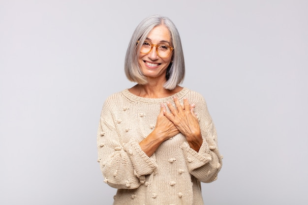 Siwa kobieta czuje się romantycznie, uśmiecha się wesoło i trzyma ręce blisko serca