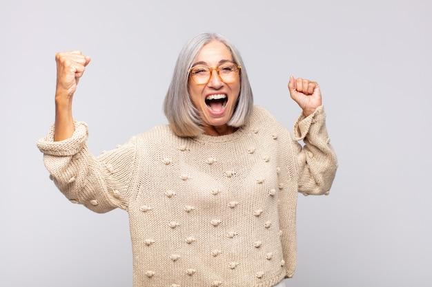 Siwa kobieta krzyczy triumfalnie, wyglądając jak podekscytowana, szczęśliwa i zdziwiona zwycięzca, świętująca
