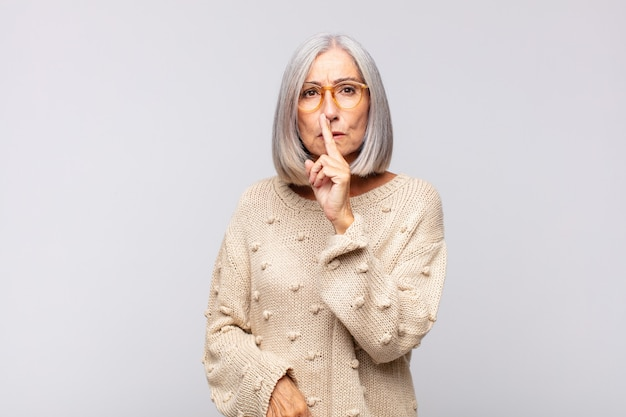 Siwa kobieta prosi o ciszę i spokój, gestykuluje palcem przed ustami, mówi cii lub zachowuje tajemnicę