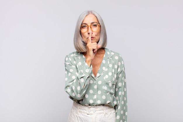 Siwa kobieta wyglądająca poważnie i krzywo z palcem przyciśniętym do ust, domagająca się ciszy lub spokoju, dochowania tajemnicy