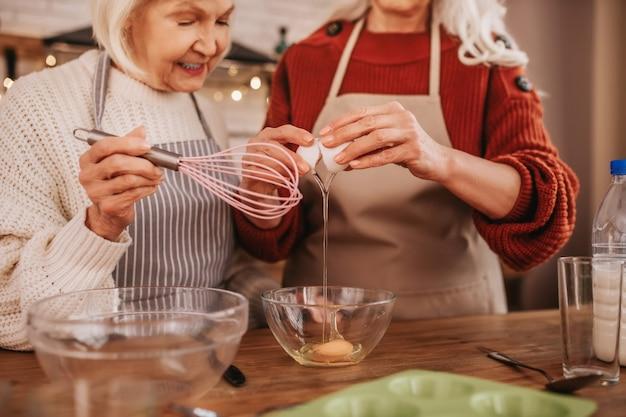 Siwe uśmiechnięte panie w fartuchach wyglądające na zajęte gotowaniem