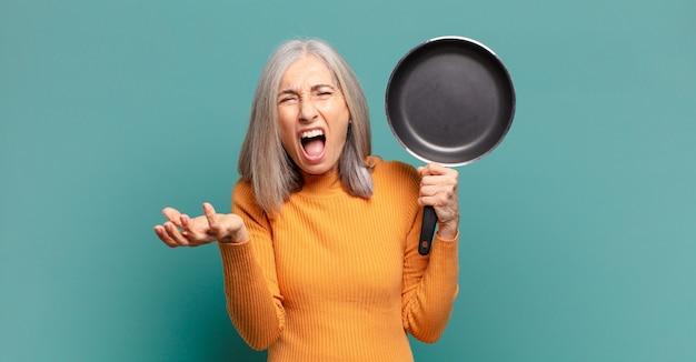 Siwe włosy dość kobieta w średnim wieku uczy się gotować na patelni