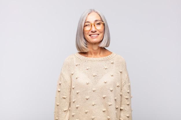 Siwe włosy kobieta szuka szczęśliwy i przyjazny, uśmiechnięty na białym tle