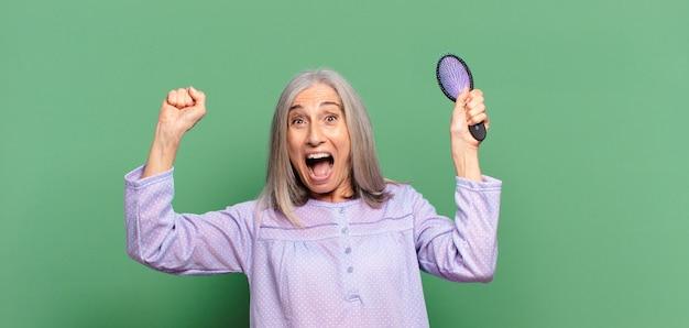 Siwe włosy ładna kobieta budzi się i nosi piżamę