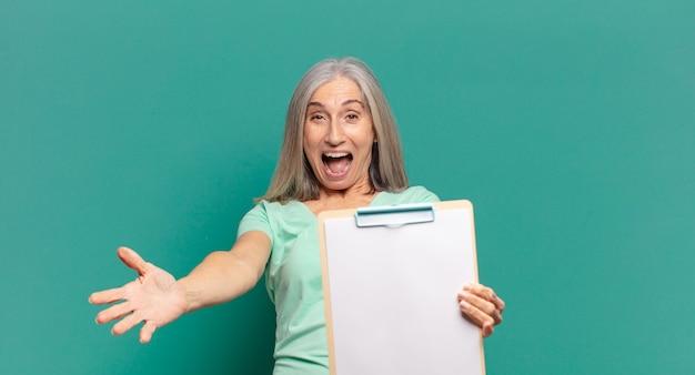 Siwe włosy ładna kobieta pokazując pustą kartkę papieru