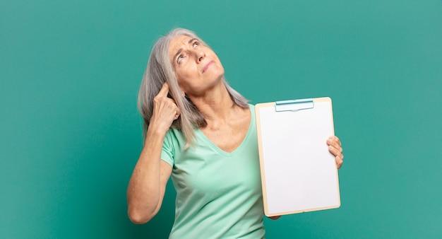 Siwe włosy ładna kobieta pokazuje pustą kartkę papieru