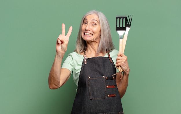 Siwe włosy ładna kobieta szefa kuchni z grilla