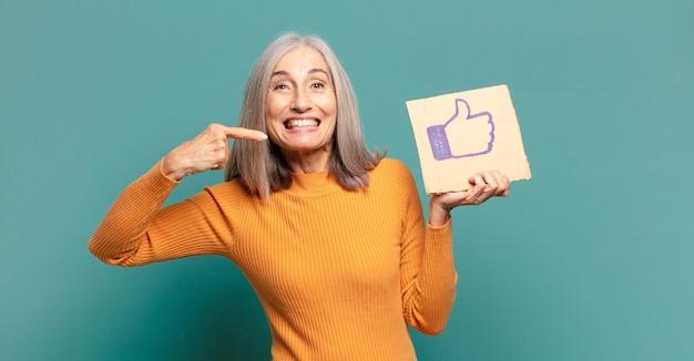 Siwe włosy, ładna kobieta trzymająca media społecznościowe jak baner