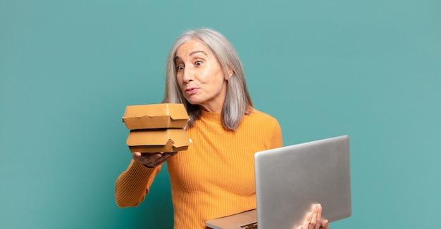 Siwe włosy ładna kobieta z laptopem. koncepcja fast foodów na wynos