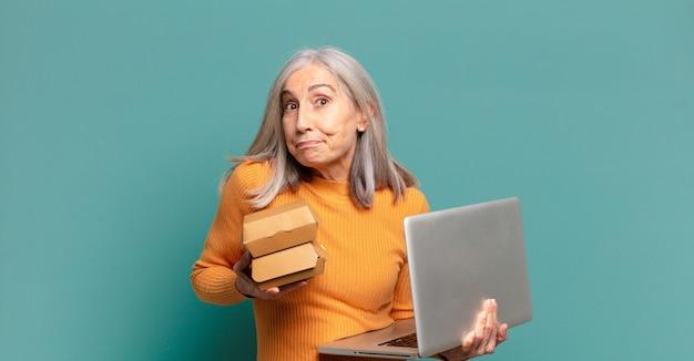 Siwe włosy ładna kobieta z laptopem. zabrać koncepcję fast food