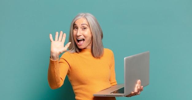 Siwe włosy ładna kobieta z laptopem.