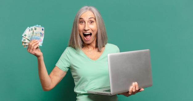 Siwe włosy ładna kobieta z pieniędzmi i laptopem