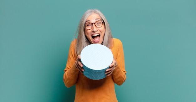 Siwe włosy ładna kobieta z pudełkiem prezentowym