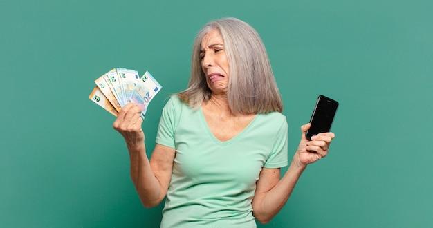 Siwe włosy ładna kobieta z rachunkami