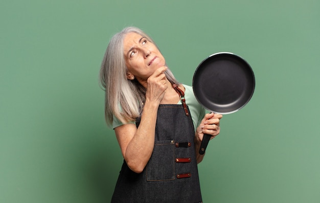 Siwe włosy ładna szefowa kuchni w średnim wieku z patelnią
