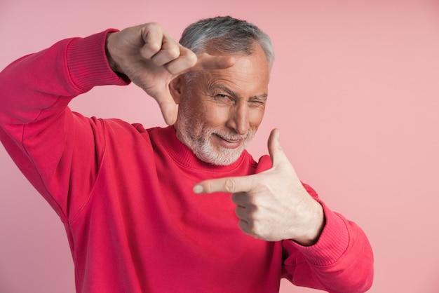 Siwobrody mężczyzna tworzy ramkę palcami