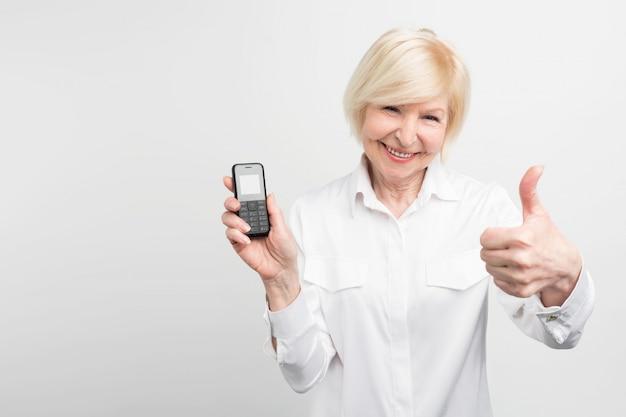 Siwowłosa dama trzyma stary telefon. woli go używać zamiast kupować i używać nowego. ta kobieta nie lubi nowych technologii.