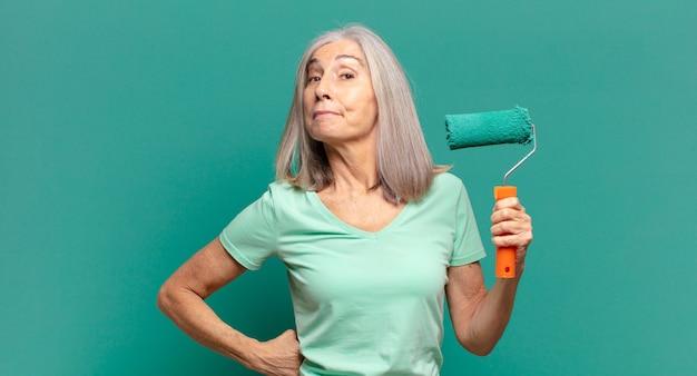 Siwowłosa kobieta w średnim wieku z wałkiem do malowania zdobiącą ścianę