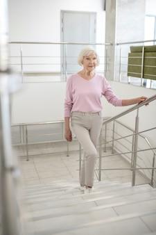 Siwowłosa kobieta w zwykłym ubraniu idąca na górę