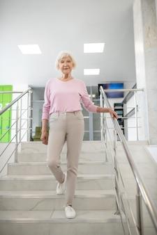 Siwowłosa kobieta w zwykłym ubraniu schodząca na dół