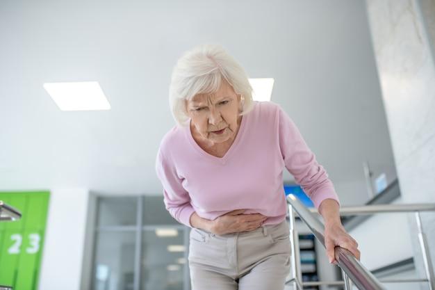 Siwowłosa kobieta w zwykłym ubraniu z bólem brzucha