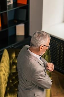 Siwowłosa osoba. widok z boku siwego mężczyzny w stylowym garniturze, stojącego i patrzącego w dół w swoim biurze