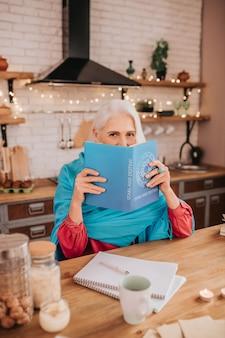 Siwowłosa piękna starsza pani w niebieskim szaliku zasłaniająca twarz książką
