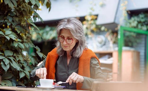 Siwowłosa starsza kobieta je pyszny deser siedząc przy stole na zewnątrz