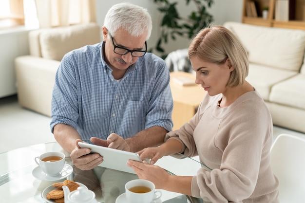 Siwowłosy emeryt na emeryturze i jego córeczka wskazujący na ekran touchpada, omawiając wideo lub informacje online przy filiżance herbaty
