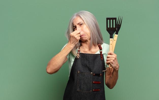 Siwowłosy ładny kucharz z grilla z narzędziami kuchennymi