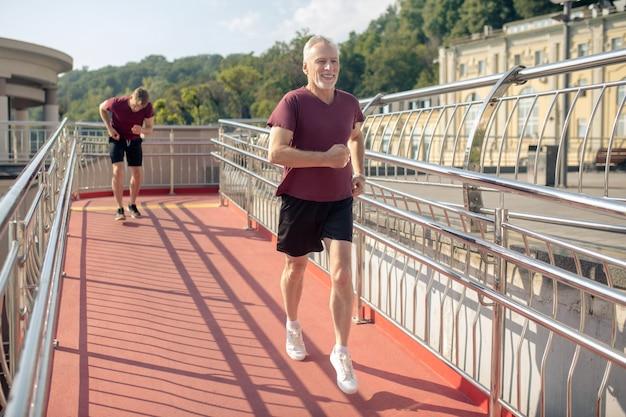 Siwowłosy mężczyzna biegnie przez most, młody mężczyzna biegnie z tyłu, źle się czując