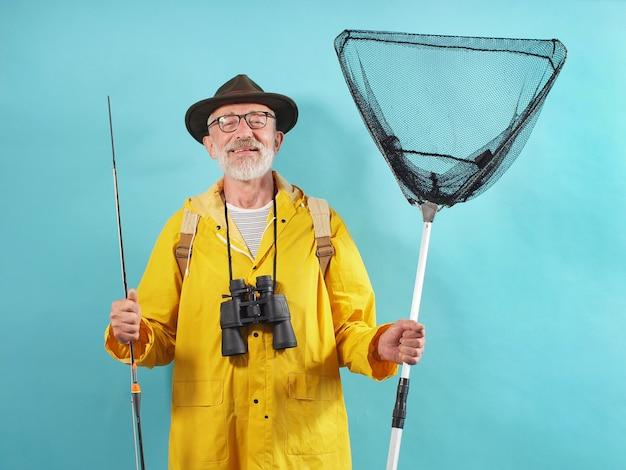 Siwowłosy mężczyzna z brodą ubrany w żółty płaszcz przeciwdeszczowy trzyma wędkę i sieć na odosobnionym tle
