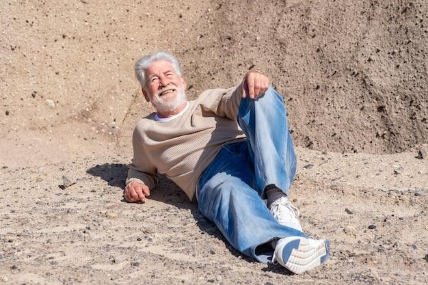 Siwowłosy starszy mężczyzna leżącej na skałach, ciesząc się słońcem w zimowy dzień. zrelaksowani starsi na wycieczce na świeżym powietrzu.