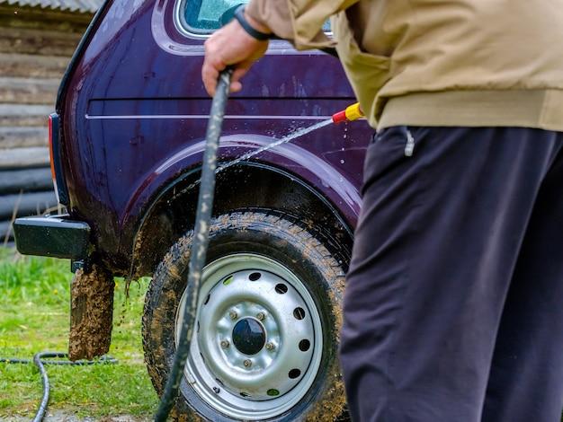 Siwowłosy starszy mężczyzna myje samochód na dworze za pomocą węża ogrodowego