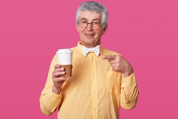 Siwowłosy starszy w jasnej koszuli i muszce trzyma dużą filiżankę kawy.
