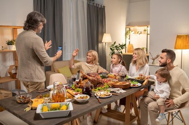Siwy dojrzały mężczyzna ze smartfonem robi zdjęcie swojej szczęśliwej blond żony i innych członków rodziny na aparacie smartfona przy świątecznym stole