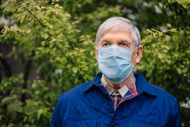 Siwy dziadek z osłoną na twarzy. stary człowiek z siwe włosy w maski ochronne medycyny na zewnątrz.